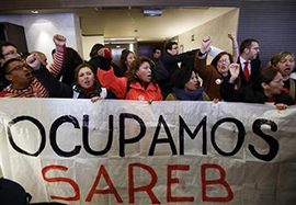 """Spanish protestors hold sign saying """"Let's occupy Sareb"""""""