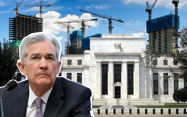 Picture of Jerome Powell sitting in front of the Federal Reserve building, which is surrounded by buildings under construction.