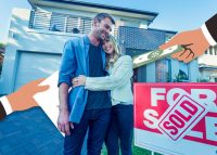 Home buyers in front of a house (Credit: iStock)