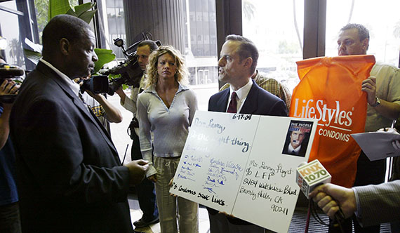 Michael Weinstein asks a security guard if he can present an oversized letter to pornography executive, Larry Flynt, asking him to voluntarily adopt a 100% condom use policy in his films (Photo by David McNew/Getty Images)