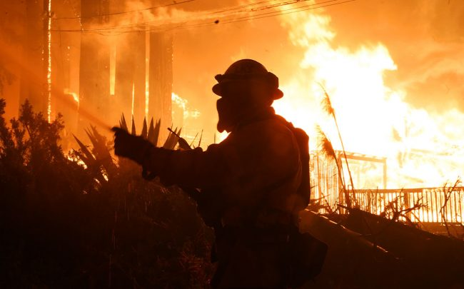 Firefighters work to protect homes surrounding residences engulfed in flames. CZU Lightning Complex fires. (Credit:  Dylan Bouscher/MediaNews Group/The Mercury News via Getty Images)