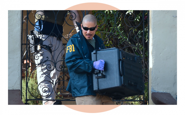 FBI agent carries a case from the home of Los Angeles Councilman Jose Huizar. The FBI served sealed warrants at the home, field and City Hall offices of Huizar. (Credit: FREDERIC J. BROWN/AFP via Getty Images)
