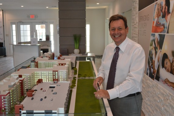 Sergio Pino, founder and president of Century Homebuilders Group, stands next to the sales model of Midtown Doral