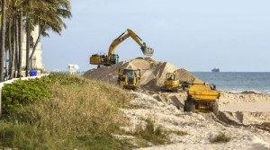 Workers place sand at Midtown Beach. ( Credit: Palm Beach Daily News)