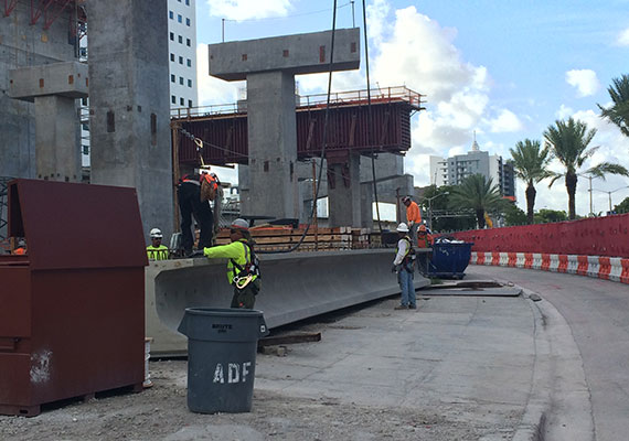 Construction workers prepare to hoist the first of 247 concrete beams for Brightline's track at MiamiCentral