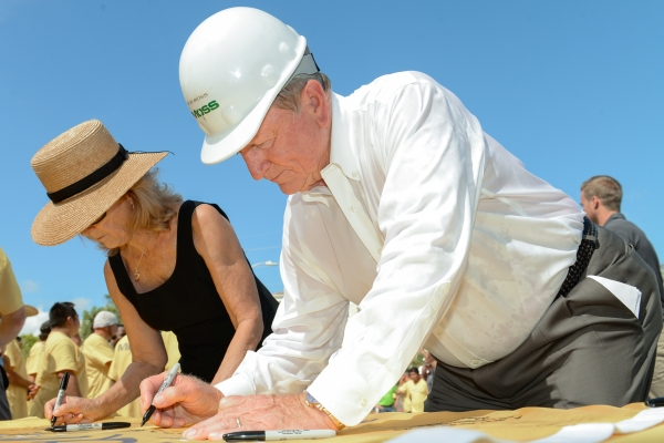 Bob Moss, chairman and CEO of Moss & Associates, signs the Brightline flag.