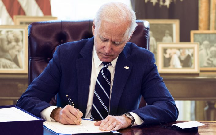 President Biden signing the $1.9 trillion COVID relief bill on March 11. (Getty)