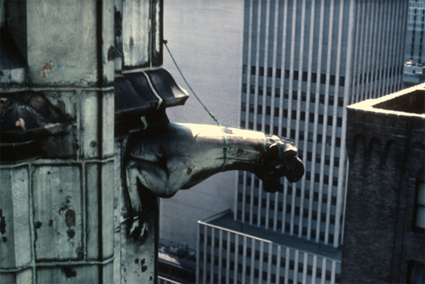 "An image from the top of the Woolworth building in the 1970s. A ""leash"" has been fitted around the gargoyle's neck to keep it from landing on pedestrians should it detach itself from the building.The Ehrenkrantz Group/Collection of Tim Allanbrook"