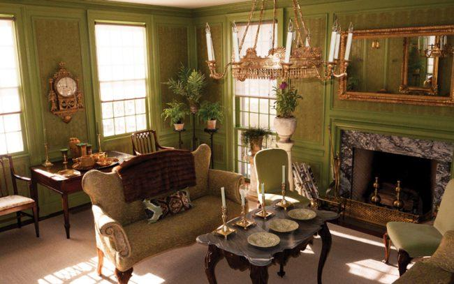 "The ""green room"" at Stewart's Bedford home features brass accents and an early-19th-century mirror, which reflects an Austrian giltwood chandelier."