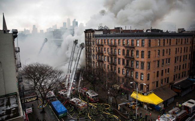 Firefighters work to extinguish a fire as a building burns after an explosion on 2nd Avenue in March 26, 2015 (Credit: Getty Images)