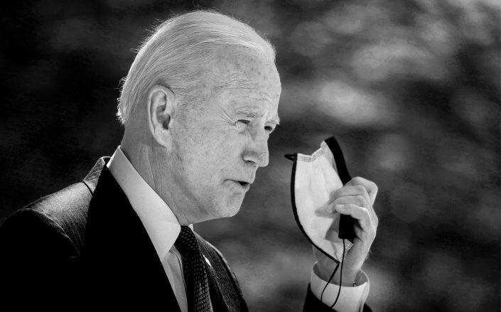 U.S. President Joe Biden removes his mask before speaking about updated CDC mask guidance. (Getty)
